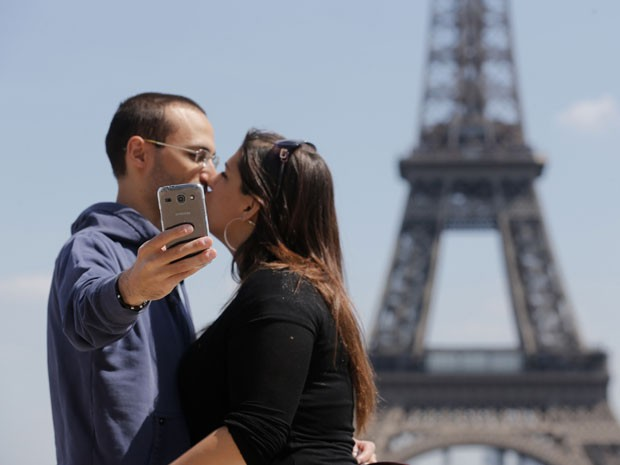 Casal faz selfie em frente à Torre Eiffel, em Paris (Foto: Christian Hartmann/Reuters)