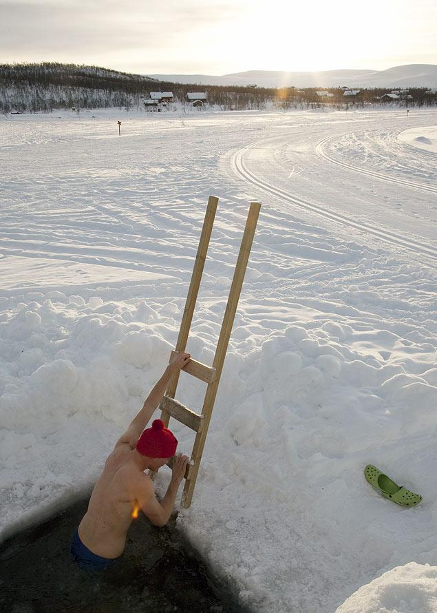 Homem entra em buraco cortado no gelo na Finlndia, a prtica  comum no pas