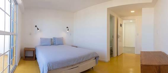 Uma das sutes para duas pessoas do hostel/Pousada:  decorao clean, muita luz e ampla varanda com vista para o mar