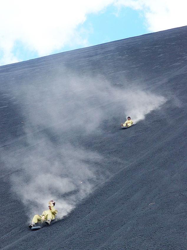 Turistas praticam volcano boarding, ou surfe em vulco, no Cerro Negro na Nicargua